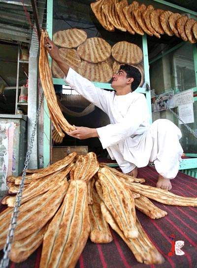 August 23: A baker arranges traditional Afghani Nan at his shop before Iftar, in Kabul.