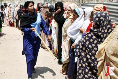 August 20: Sorry for these ladies: A policewoman uses a stick to maintain the queue near a provincial government truck as women line up to flour and sugar on discounted rates