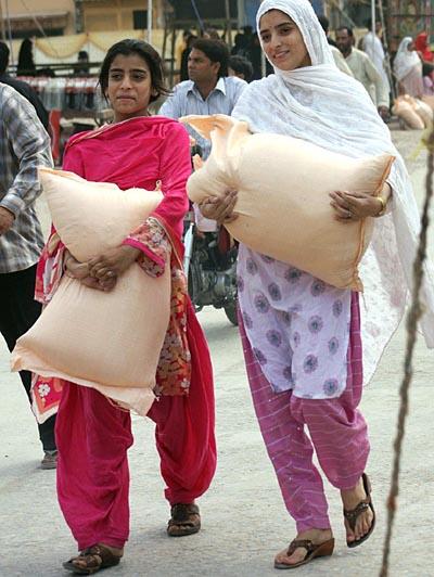 August 31: Women return after buying flour on subsidized rates from Ramadan Sasta Bazaar near Committee Chowk.