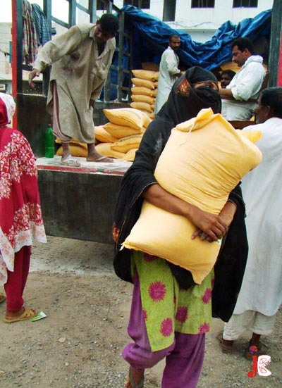 August 18:  A woman carrying wheat flour bag on government controlled rate at the cost of Rs.200, from a truck in Multan