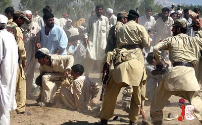 September 16: Pakistani FC soldiers try to avoid a stampede situation at a relief camp set up by the paramilitary Frontier Corps in Mohmand Agency