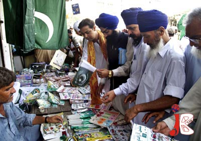 August 11: Sikh Pakistanis select national flags and badges from a roadside stall as the preparations for national day celebration, are in full swing around the country