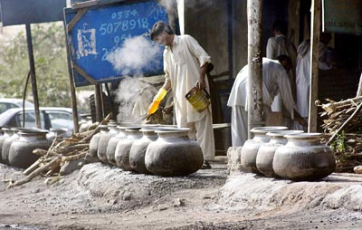 October 09: A man prepares food for the devotees at the shrine of Barri Imam at Nurpur Shahan