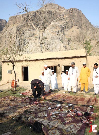 August 28: Pakistani security personnel collect evidence at the site of a blast in Mohmand Agency. More than 20 soldiers of Khasadar force were killed while eating to conclude their fast in Mohmand Agency area