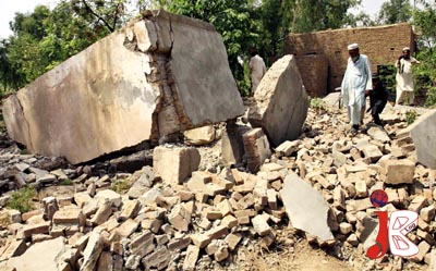 August 12: Pakistani people collect the rubble at the Lashkar-e-Islami Office after it was destroyed in an operation by Security Forces in Bara, Khyber Agency.