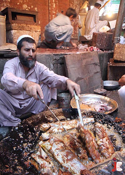 September 05: A man prepares fried fish for Iftar near Ghanta Ghar, Peshawar.