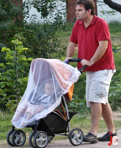 September 30: A foreign man has installed a sheet to protect his child from mosquitoes, during walk alongside a road in the capital