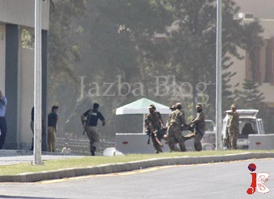 October 10: Pakistan army commandos carry the body of a militant wearing military uniforms and tried to break into Pakistan's army headquarters