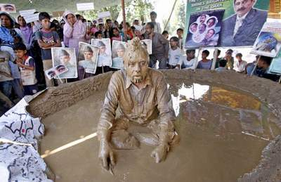 June, 23: Former Minister for Minorities J.Salik, protesting by sitting in mud