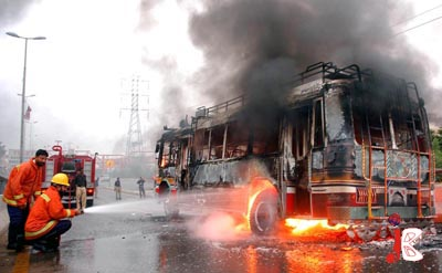 August 17: Fire fighters trying to douse fire on a mini-bus charred by angry mobs at Nagan Chowrangi flyover in protest against killing of head of outlawed Sipah-e-Sahaba Pakistan, Allama Ali Sher Haidri, who was gunned down in District Khairpur in wee hours of Monday.