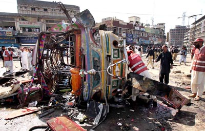 October 09: Pakistani security personnel and rescue officials inspecting the blown passenger bus after a massive suicide car bomb ripped through Khyber Bazaar in Peshawar, leaving at least 49 people dead and injured at least 100. The blast took place exactly in a shopping area close to the northwestern city's main Khyber Bazaar.
