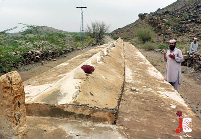 August 18: A man offers Fateha at a 120 feet long grave in FR Bannu Area, Daryoba Agency