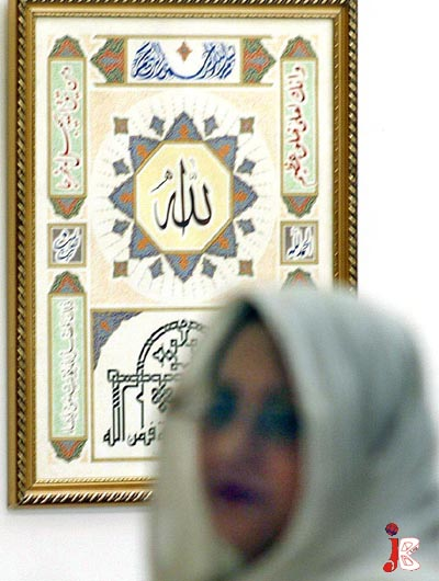 September 16: A woman walks past the art pieces of calligraphy displayed during an exhibition at Pakistan National Council of Arts.