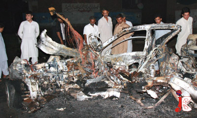 August 22: People gather near a car which was destroyed in a remote controlled blast near Hayatabad Medical Complex in Peshawar. Two people were killed in the blast