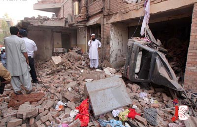 October 15: People inspect the damage after a car bomb blast in Gulshan-e-Rehman Colony, Kohat road in Peshawar.