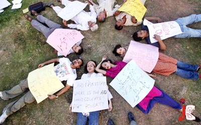 September 29: Students and Activists of civil society lie on the ground during a demonstration against price hike, hoarding, Kerry Lugar Bill and alleged presence of Black Water in Pakistan, outside National Press Club.