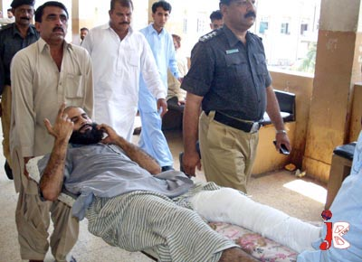 October 02: Pakistani policemen escort an injured man who is suspectedly involved in the killing of Balochistan Provincial Minister, in Gulistan-e-Johar.