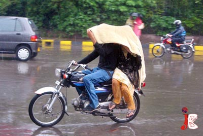 August 21:  Motorcyclists use a towel to shelter themselves from rain in the provincial capital