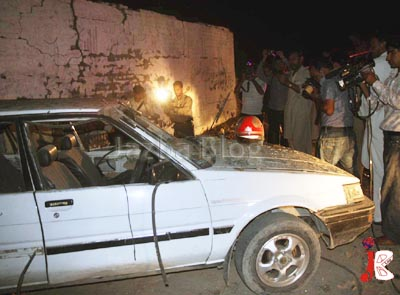 August 20: People gather near a damaged car at the site of a blast at Misryal Road, Dhoke Syedan near a police picket. Four policemen have been reportedly injured in the blast, which appeared to be a planted bomb