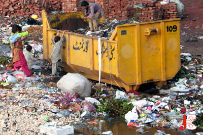 August 24: Scavenger children are in search of useable items in a garbage can installed by city district government Faisalabad.