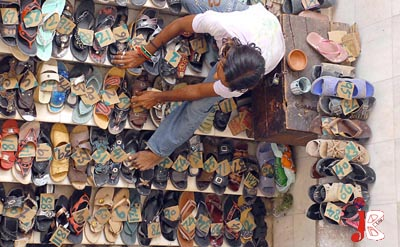 August 28: A man applies tokens to the shoes of the Muslims outside Data Darbar Mosque in Lahore