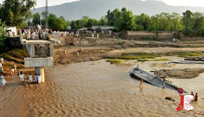 August 17: People look at the Kalu Khan Bridge in Swabi, which has been driven by flood water