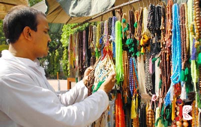 August 18: Back in Fashion: A man buys rosaries (tasbeh), at a stall outside a mosque ahead of the holy month of Ramadan