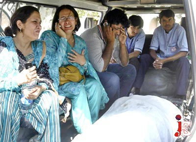 October 05: The officials weep over the body of their female receptionist, Gul Mukhtar, the victim of UN Food Program office F-8/3 blast to in ambulance.