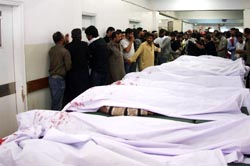 Pakistani people weep near the bodies of the people who lost their lives in a motorcycle bomb blast in Karachi